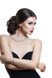 Portrait of a beautiful young woman with a professional make-up on a white background. The ideal beauty. Red lips. Necklace from stones on the neck
