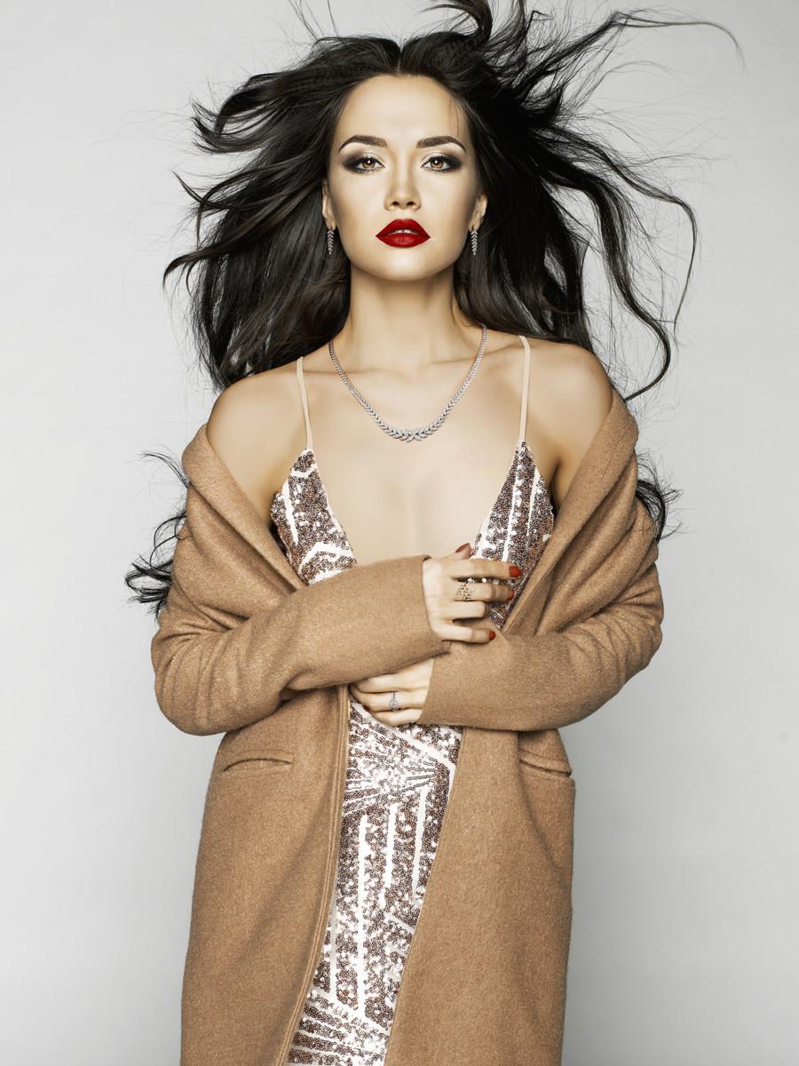 Beautiful sexy brunette model in fashion clothes posing in studio. Wearing coat, evening dress