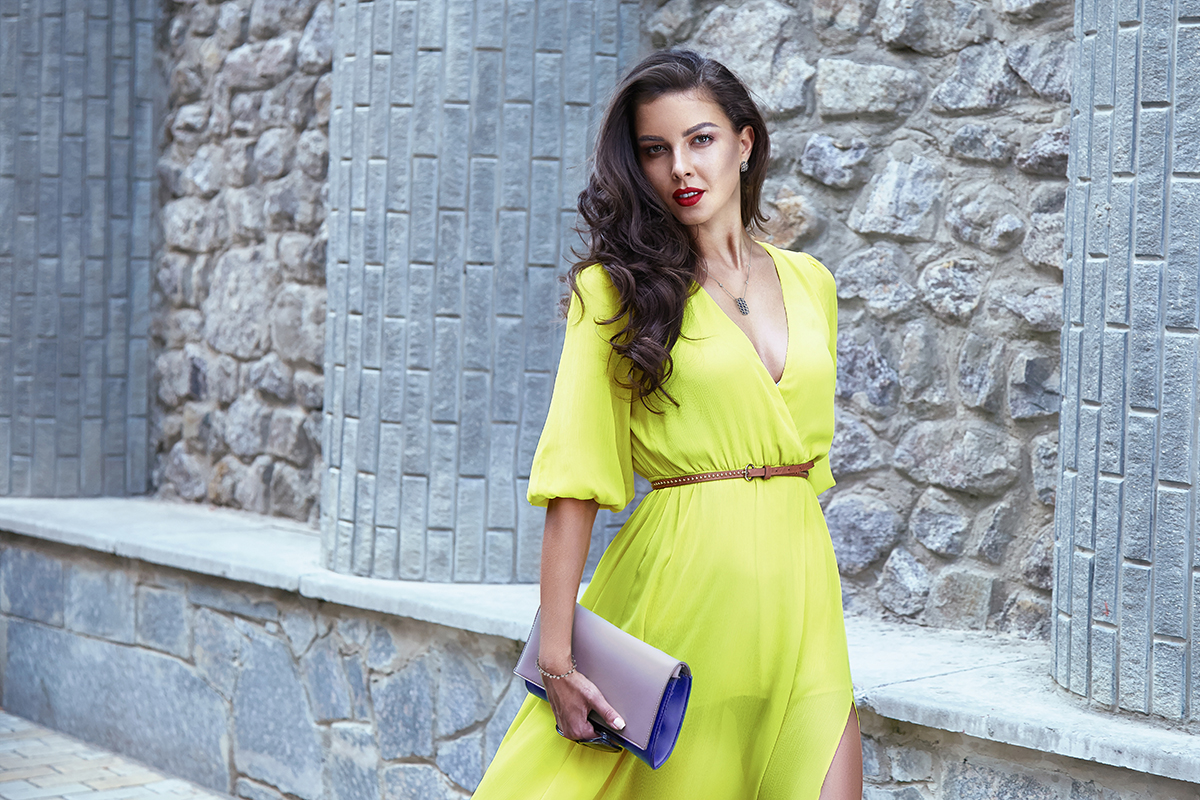 Beautiful sexy brunette girl dark hair evening makeup red lipstick long silk dress perfect shape tanned body, accessories jewelry watches handbag walking down the street, going to a meeting or a party