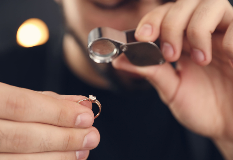 Male jeweler evaluating ring in workshop, closeup